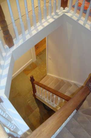 Staircase to hall with natural stone floor